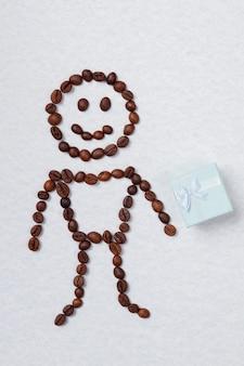 コーヒー豆でできた体をした笑顔の象徴的な男。白いリボンが付いた青いギフト ボックス。白で隔離されます。