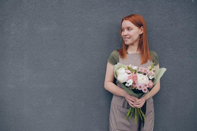 Улыбающаяся талантливая молодая женщина-флорист с рыжими волосами в фартуке стоит у серой стены и держит красивый букет в оберточной бумаге