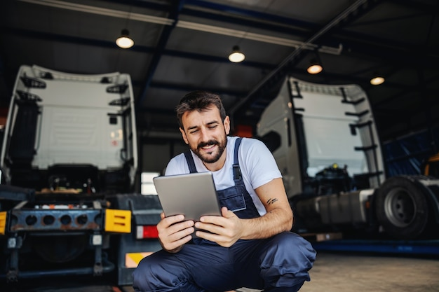 Smiling tattooed bearded blue collar worker in overalls using tablet to check on delivery while crouching in garage of import and export firm