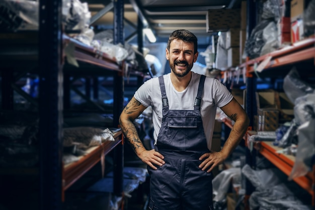 Smiling tattooed bearded worker in overalls standing in storage with hands on hips.
