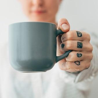 一杯のコーヒーを持っている笑顔の入れ墨の女性