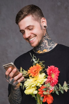 Smiling tattooed young man with pierced ears and nose holding bouquet using smartphone