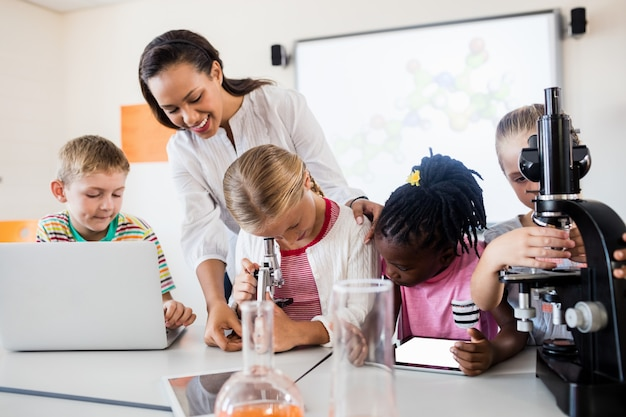 Smiling teacher helping pupils