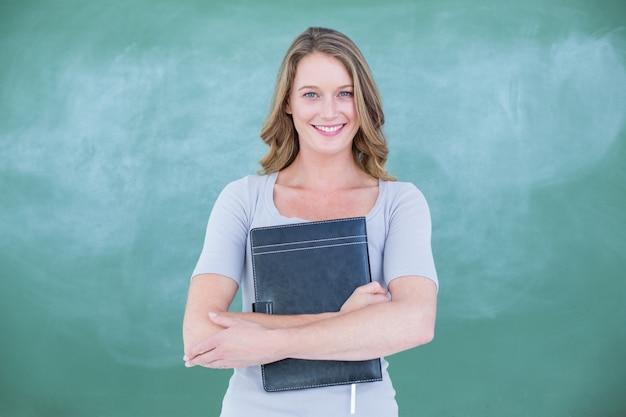 Smiling teacher holding notebook in front of blackboard