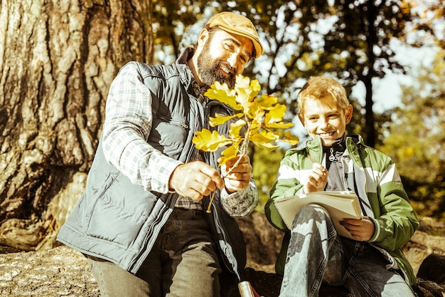 A smiling teacher teaching his pupil in the forest on a fine day