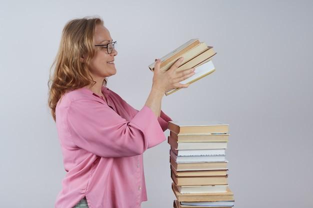眼鏡をかけた笑顔の先生は、山の肖像画に本を積み重ねます