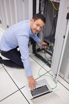 Smiling technician inserting a usb