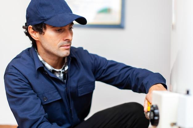 Улыбающийся техник ремонтирует водонагреватель