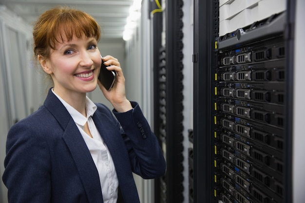 Улыбающийся техник разговаривает по телефону, глядя на сервер