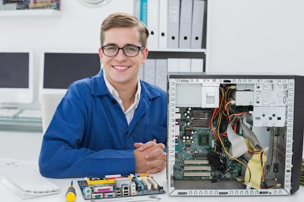 壊れたコンピュータで働く笑顔の技術者