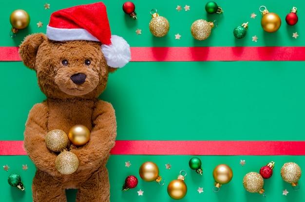 Улыбающийся плюшевый мишка, держащий рождественские безделушки на размытом фоне с украшениями.