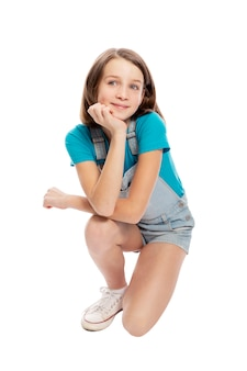 Smiling teen girl in denim overalls squats. isolated on a white background