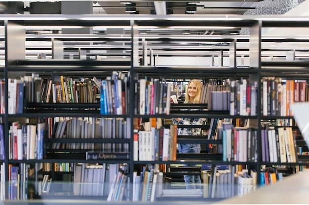 Улыбающаяся девушка-подросток в библиотеке