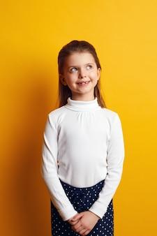 Улыбающаяся девочка-подросток задумчиво смотрит вверх на желтом фоне