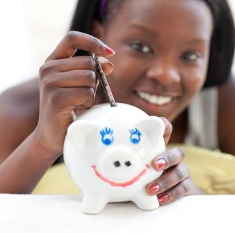 Smiling teen girl putting money in a piggy-bank