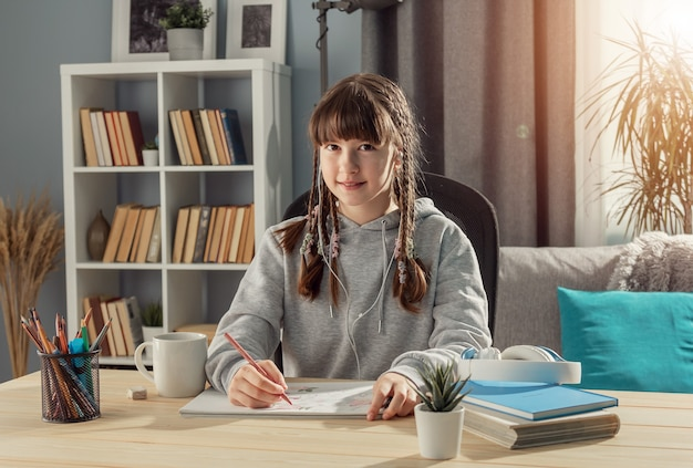 Smiling teen girl sitting at desk looking at camera, studying from home, front view
