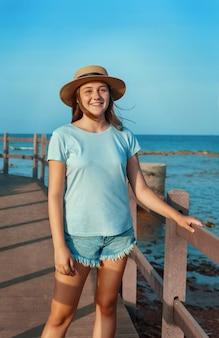 Улыбающаяся девочка-подросток, стоящая на деревянной дорожке у моря на закате, в голубой футболке и соломенной шляпе. концепция летнего путешествия