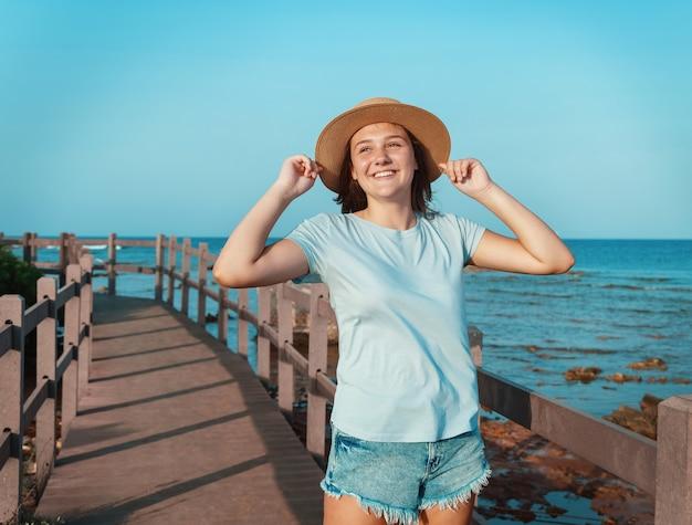 Улыбающаяся девочка-подросток стоит на деревянной дорожке у моря на закате в голубой футболке и касается обеими руками своей соломенной шляпы. концепция летнего путешествия