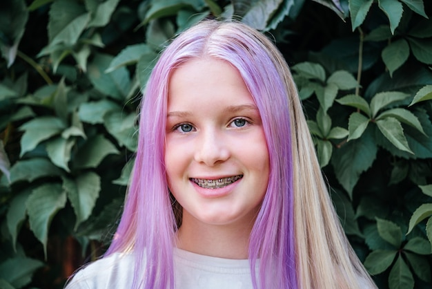 Smiling teen girl wearing dental braces, cute caucasian girl with pink hair wearing orthodontic brackets