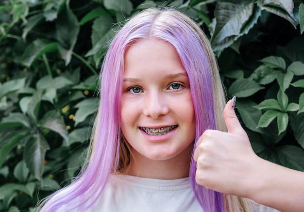 ピンクの髪を着ているかわいい白人の女の子を親指で歯列矯正器を身に着けている10代の少女を笑顔...