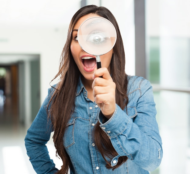 彼女の左手で虫眼鏡を保持している十代の笑顔
