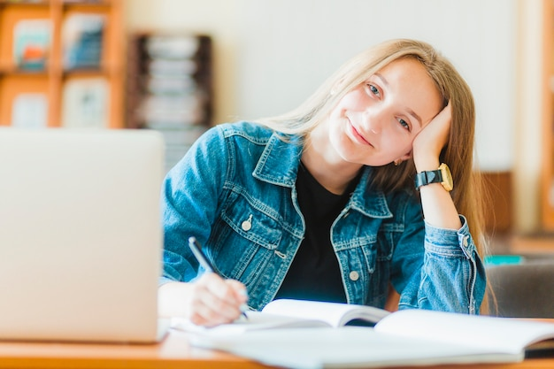 Smiling teen making notes near laptop