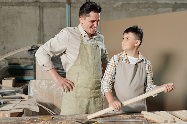 Smiling teenage boy in apron standing with polished wooden plank and enjoying carpentry work with father