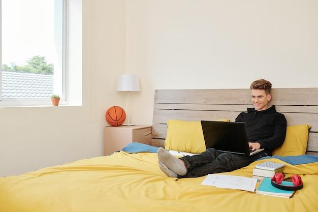 Улыбающийся мальчик-подросток в толстовке с капюшоном сидит на кровати с ноутбуком, кодирует, играет в игры или посещает онлайн-класс