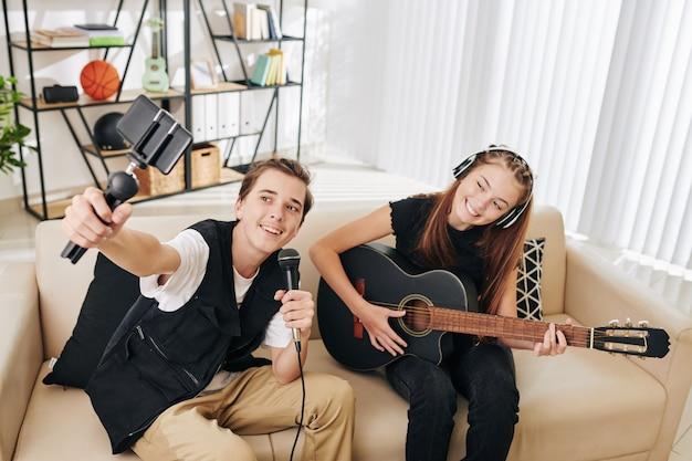 여동생이 기타를 연주 할 때 노래하는 자신의 비디오를 촬영하는 십대 소년 미소 짓기