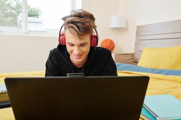 열린 노트북으로 침대에 앉아 자신의 스마트 폰에서 문자 메시지를 확인하는 십 대 소년 미소