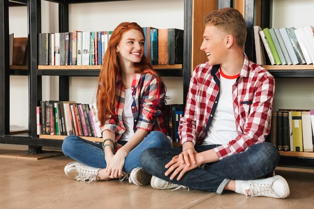 Smiling teenage couple sitting on a floor at the bookshelf