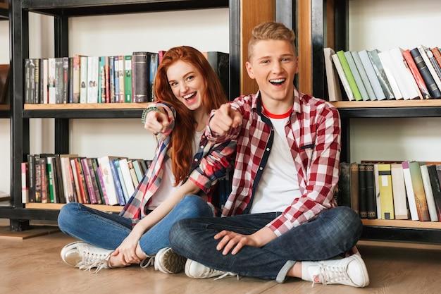 床に座って笑顔の10代のカップル