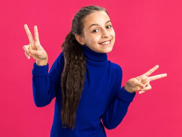 ピンクの壁に分離された平和のサインをやって笑顔の10代の少女