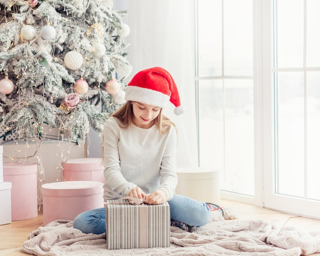 クリスマスプレゼントを持って笑顔の10代の少女