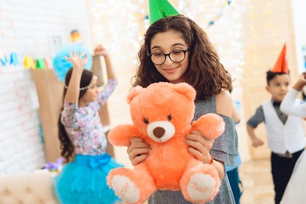 Улыбающаяся девочка-подросток в очках держит плюшевого мишку