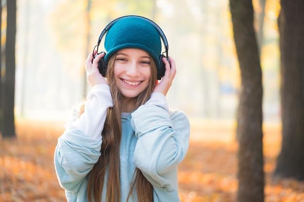 屋外のヘッドフォンで笑顔の 10 代の少女