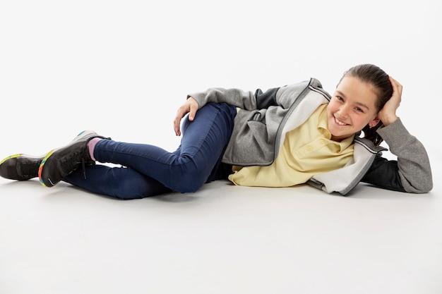 까마귀와 청바지에 웃는 십 대 소녀는 바닥에 놓여 있습니다.
