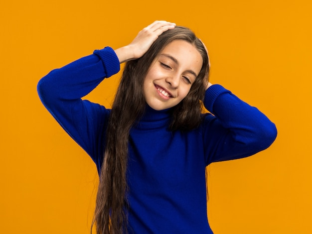 Smiling teenage girl keeping hands on head squinting eyes looking at front isolated on orange wall