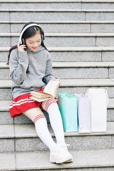 Улыбающаяся девочка-подросток слушает музыку и читает книгу, сидя на ступеньках после покупок