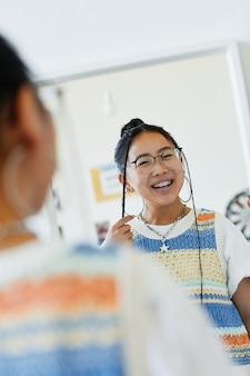 Улыбающаяся девочка-подросток, глядя в зеркало