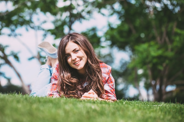 Smiling teenage girl  lying on the grass in the park