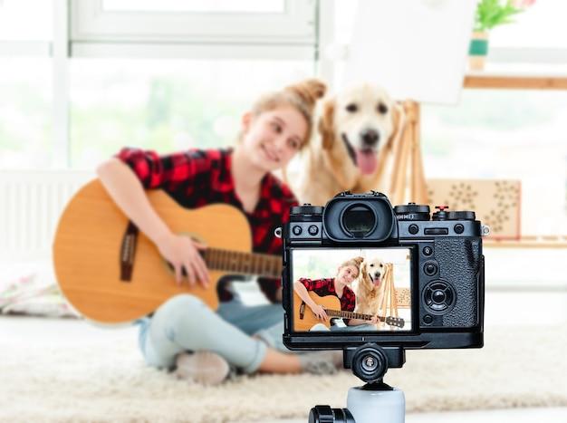 明るい部屋でギターを弾く10代の少女の笑顔