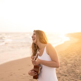 해변에서 우쿨렐레를 연주 웃는 십 대 소녀