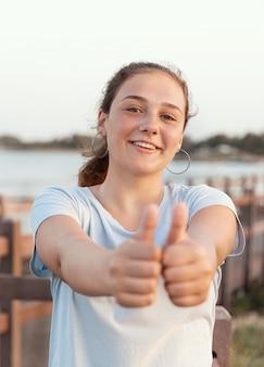 10대 소녀가 큰 엄지손가락을 치켜들고 해질녘 바다 근처에서 밝은 파란색 티셔츠를 입고 웃고 있습니다. 헤드샷. 선택적 초점입니다.