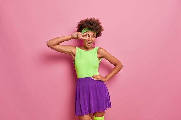 웃는 십대 소녀는 승리의 몸짓을 보여주고, 밝은 셔츠와 치마를 입고, 행복한 분위기에 있고, 삶을 즐기고, 행복하게 옆으로 보이며, 성공을 축하합니다.