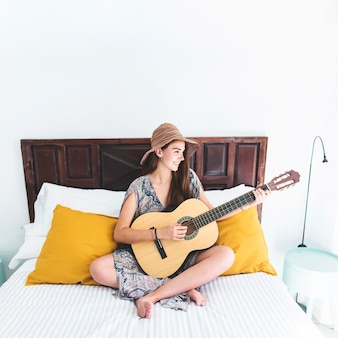 Smiling teenage girl sitting on bed playing guitar in bedroom