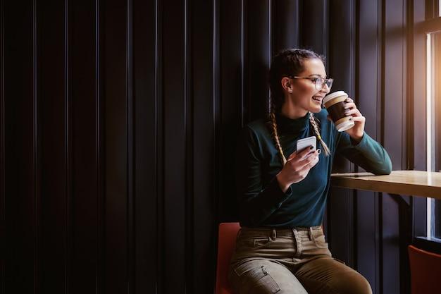 Улыбающаяся девочка-подросток сидит в кафетерии рядом с окном, пьет кофе и держит смартфон, глядя через окно.