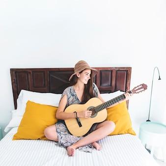 Улыбаясь девочка-подросток, сидя на кровати, играя на гитаре в спальне