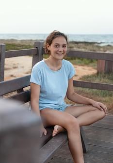 Улыбающаяся девочка-подросток сидит на деревянной скамейке у побережья