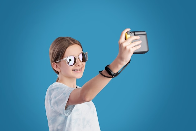 Smiling teenage girl in sunglasses and t-shirt holding photocamera in front of herself while making selfie against blue background